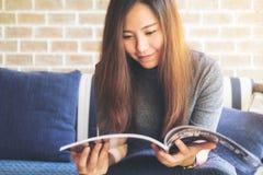 读杂志的一名美丽的亚裔妇女在现代咖啡馆的蓝色沙发 免版税库存照片