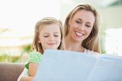 读杂志的母亲和女儿 免版税图库摄影