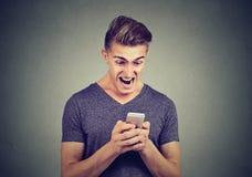 读正文消息的沮丧的恼怒的人在尖叫的智能手机 库存图片