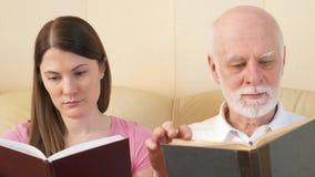 读物理印刷品书的父亲和女儿 传统古典纸读书的概念 影视素材