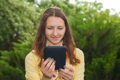 读电子书的青少年的女孩 免版税图库摄影