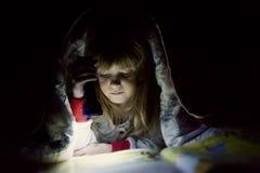 读的小女孩床 免版税库存照片