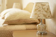 读的灯在以卧室的舒适内部的为背景一个床头柜 r 免版税库存图片