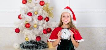 读秒新年度 女孩孩子圣诞老人有计数时间的时钟激动的愉快的面孔的帽子服装对新年 最后一刻直到 免版税图库摄影