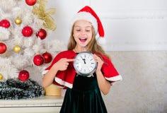 读秒新年度 计数时间的女孩孩子圣诞老人帽子服装举行时钟激动的愉快的面孔表示对新年 为时 免版税图库摄影