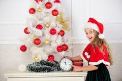 读秒新年度 计数时间的女孩孩子圣诞老人帽子服装举行时钟激动的愉快的面孔表示对新年 为时 库存图片