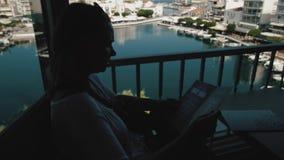 读菜单和做的顺序在咖啡馆大阳台,地方烹调概念年轻美丽的旅客妇女 影视素材