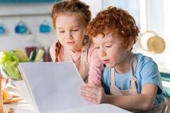 读菜谱的被聚焦的小孩,当一起时烹调 免版税库存照片
