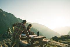 读迁徙的地图的Coouple远足者在背后照明,背面图的桌 在阿尔卑斯的冒险探险 库存照片