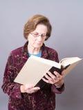 读高级妇女的书玻璃 免版税图库摄影