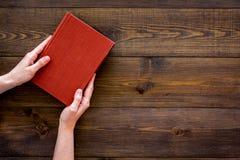 读leasure的 手采取与空的盖子的精装书书在文本的黑暗的木背景顶视图空间 免版税库存照片