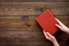 读leasure的 手采取与空的盖子的精装书书在文本的黑暗的木背景顶视图空间 图库摄影