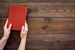 读leasure的 手采取与空的盖子的精装书书在文本的黑暗的木背景顶视图空间 库存图片