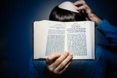 读Machzor祈祷的书的犹太男性佩带的Kippah 免版税图库摄影