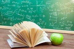 课本和绿色苹果在书桌上有绿色委员会的 免版税库存照片