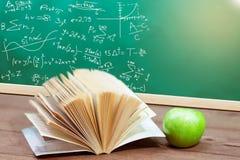 课本和绿色苹果在书桌上 免版税库存图片