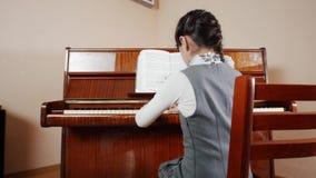 课程音乐 女孩钢琴使用 滑子视图使用从女孩的后面 影视素材