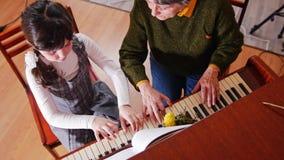 课程音乐 弹钢琴,长辈老师的女孩坐近并且使用与女孩 顶视图 股票录像
