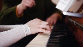 课程音乐 弹钢琴,长辈老师的女孩坐近并且帮助与使用 从右边的看法 影视素材