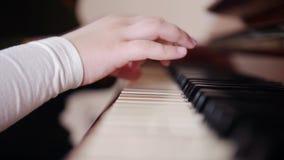 课程音乐 弹钢琴,长辈老师的孩子坐近并且帮助与使用 从右边的看法 股票录像