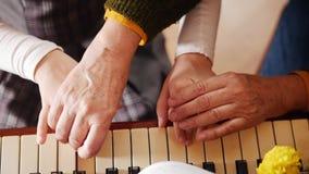课程音乐 演奏钢琴、更旧的老师与使用的女孩立场在她附近和帮助 顶视图 影视素材
