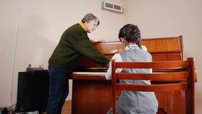 课程音乐 演奏钢琴、更旧的老师与使用的女孩立场在钢琴附近和帮助在钢琴 滑子视图 影视素材