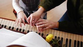 课程音乐 演奏钢琴、更旧的老师与使用的女孩立场在钢琴附近和帮助 顶视图 影视素材
