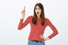 谁是睡觉这个的女孩在楼上 恼怒的失望的欧洲妇女,握在臀部的手和向上指向与 免版税库存图片