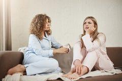 谁需要心理学家,当您有最好的朋友 两名妇女坐在睡衣的沙发在舒适屋子里,谈论 库存照片