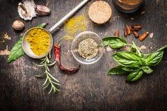 调味品和香料创造性烹调的在黑暗的土气木背景,顶视图 免版税库存图片