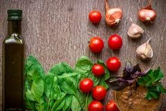 调味汁做的新鲜的有机成份:菠菜,蕃茄,新芽,蓬蒿,在土气背景,顶视图的橄榄油 免版税库存照片
