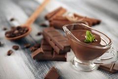 调味汁瓶用在木桌上的鲜美溶解的巧克力 库存图片