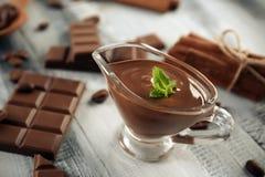 调味汁瓶用在木桌上的鲜美溶解的巧克力 库存照片