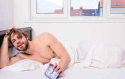 调控您的bodie时钟 供以人员有不剃须的被弄乱的头发警惕的面孔休息早晨好 人不剃须的被放置的床举行 库存图片