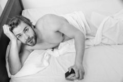 调控您的bodie时钟 睡眠政权习性 人不剃须的位置床举行闹钟 人不剃须的有胡子的警惕的面孔 免版税库存照片