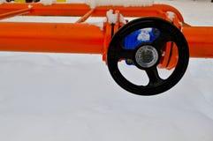 调控打开的工业切断防护管子配件黑阀门,关闭在有耳轮缘的铁橙色金属管子 库存图片