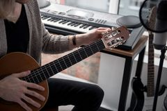 调整他的吉他的男性音乐家 库存照片