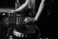 调整声音的女性DJ的手在迪斯科聚会期间 库存照片