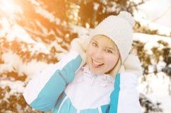 调整她的帽子的美丽的白肤金发的微笑的女孩 库存图片