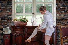 调整她的长袜的舞蹈家在梳妆台附近 库存照片