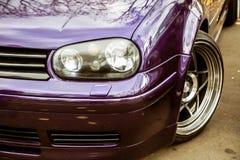 调整的紫色糖果修改过的车灯上色了驾驶低底盘汽车兜风者 有的姿态习惯汽车在街道上的伪造的优美的轮子逗留 库存图片