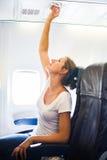 调整空调的女性乘客 图库摄影