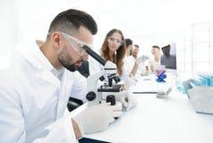 调查一个显微镜的研究员在一个现代实验室 免版税库存照片