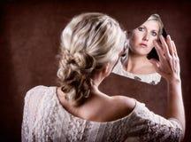 调查一个残破的镜子的妇女 免版税库存照片