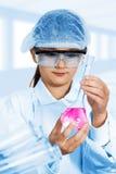 调查一个烧瓶的小女孩红色液体 库存照片