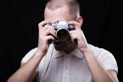 调查一台老照相机的透镜的一个年轻人 免版税库存照片