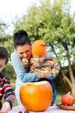 调查万圣夜南瓜的母亲和婴孩 免版税库存照片