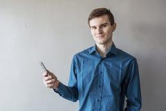 调查与一个电话的照相机的一个英俊的人的画象在他的手上 在一件绿色衬衣 深色的眼睛绿色 他微笑 免版税库存图片