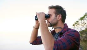 调查与双筒望远镜的距离的年轻人 免版税库存图片