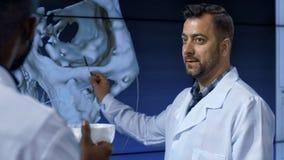 调查人的头骨的医学家 库存图片